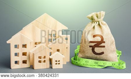 Residential Houses And A Ukrainian Hryvnia Money Bag. Mortgage Loan. Buying, Fair Price. Property Re