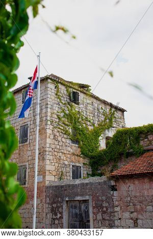 Beautiful Old Stone House In The Village Of Milna Overgrown With Green Plants, Croatian Flag On A Po