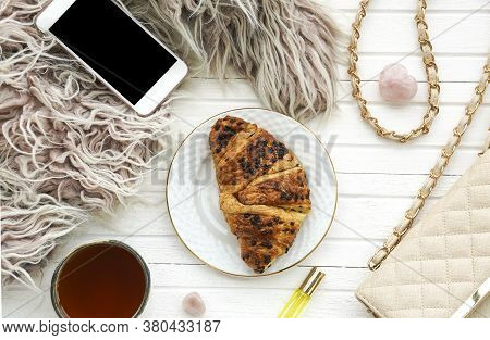 Morning Flatlay With Croissant And Tea, Smartphone, Handbag On White Wooden Background.