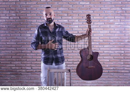 Humble Young Adult Male Holding An Acoustic Guitar After A Performance.