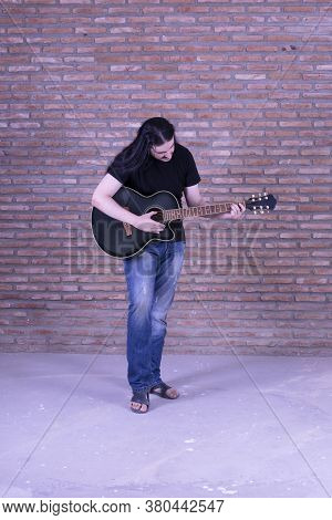 Young Male Guitarist Playing In Casual Clothes