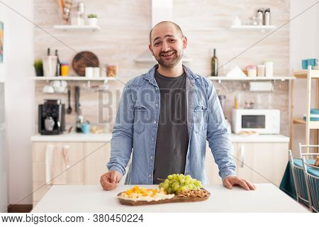 Cheerful Young Man In Kitchen Smiling Looking At At Camera With Various Cheeseboard And Grapes On Th