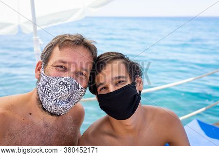 Man and boy with masks on beach jetty