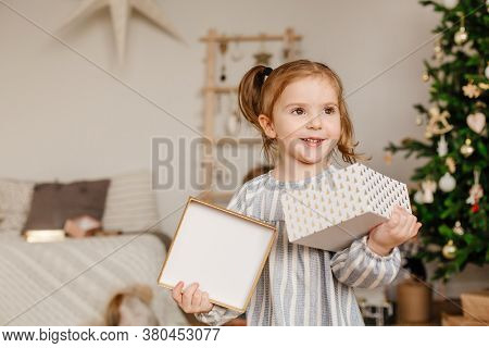 A Three-year-old Girl Holds A Gift Box In Her Hands And Smiles. Children, Family And Holiday Concept