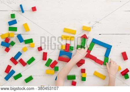 The Child Builds Geometric Shapes From Wooden Multi-colored Cubes. Top View On Many Colored Cubes On