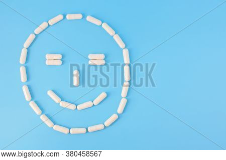 Capsules Arranged In Smilng Face. Smiling Face Made From White Pills On A Blue Background. The Conce