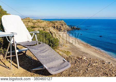 Empty Folding Camp Chair On Cliff Above Cabezo Negro Beach, Spanish Landscape Along Almeria Coast. H