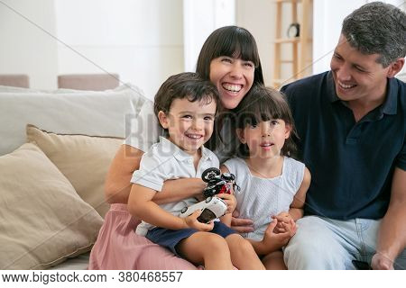 Cheerful Funny Parents And Two Kids Watching Funny Movie At Home, Sitting On Couch In Living Room An