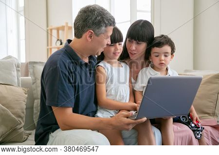 Positive Parents Holding Two Children On Lap, Sitting On Couch All Together, Watching And Discussing