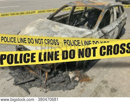 Burnt Out Car Wreck With Yellow Police Tape With Text Police Line Do Not Cross. Selective Focus On Y