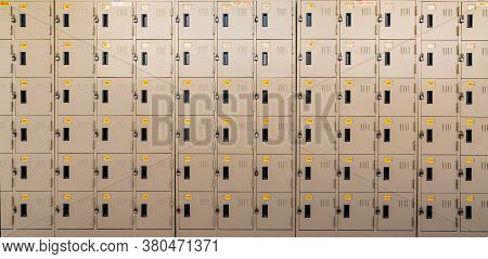 Closeup Beige Locker With Lock And Numbered Yellow Tags At Locker Room. Locker For Safety And Securi
