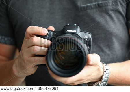 Barcelona, Spain - July 31, 2020: Male Hand Holding Brand New Mirrorless Digital Camera Canon R5 Clo