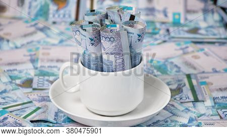 Kazakhstan Tenge In A Cup On The Table.a Lot Of Kazakh Money.sawing The Budget,the Subsistence Minim