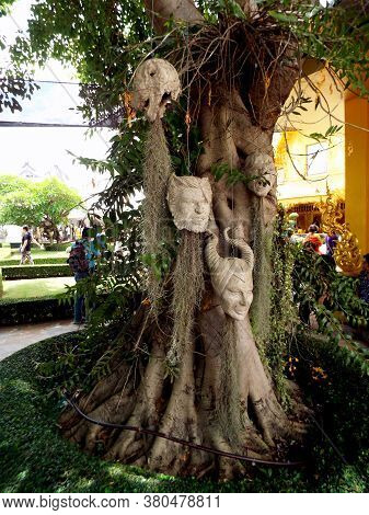 Chiang Rai. Thailand, June 17, 2017: Wat Rong Khun. Modern Patterned Heads Hang From The Trees As Th