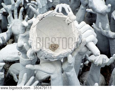 Chiang Rai. Thailand, June 17, 2017: Wat Rong Khun. Detail Of The Bowl With Coins Held By Hands In T