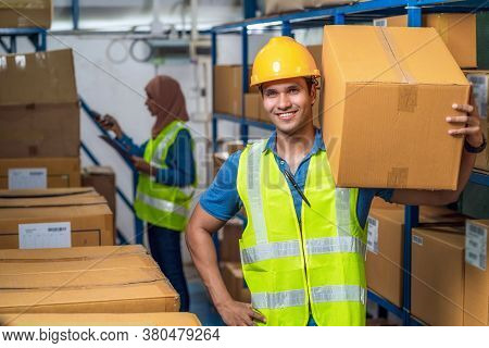 Idian Worker Man Holding Cardboard Box And Walking With Muslim Worker Woman Scanning Bar Code And Qr