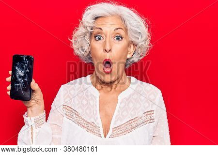 Senior grey-haired woman holding broken smartphone showing cracked screen scared and amazed with open mouth for surprise, disbelief face