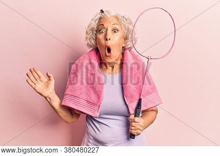 Senior grey-haired woman holding badminton racket wearing towel scared and amazed with open mouth for surprise, disbelief face