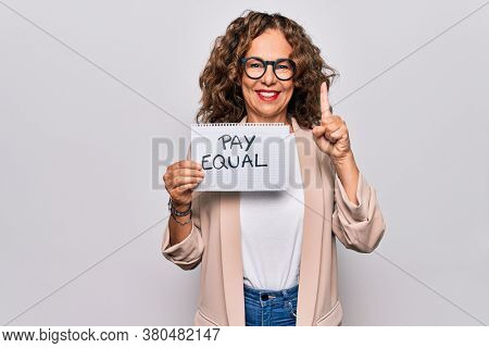 Middle age beautiful woman holding paper with pay equal message over white background smiling with an idea or question pointing finger with happy face, number one
