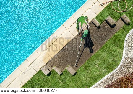 Caucasian Professional Landscaper Installing Brand New Grass Turfs Around Residential Swimming Pool.