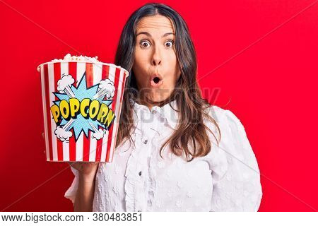 Young beautiful brunette woman eating pack of popcorns over isolated red background scared and amazed with open mouth for surprise, disbelief face