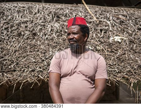An African Older Man In Red Muslim Taqiyyah Fez Hat Posing With A Stick For Lame People On Yard Near
