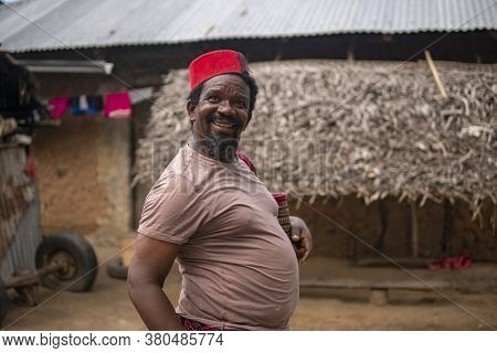 Portrait Of An African Older Man In Red Muslim Taqiyyah Fez Hat Posing With A Stick For Lame People
