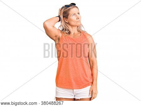 Middle age fit blonde woman wearing casual summer clothes and sunglasses confuse and wondering about question. uncertain with doubt, thinking with hand on head. pensive concept.