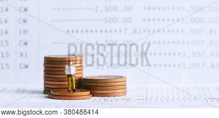 Miniature People: Businessman Standing On Bank Passbook. Retirement Planning And Pension. Money Savi