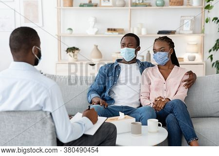 Family Therapist Talking To Black Couple Sitting In Protective Masks On Couch At Office, Free Space