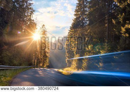 Blurred Car Is Driving Fast On Mountain Road In The Autumn Forest In The Evening Travel By Car Conce