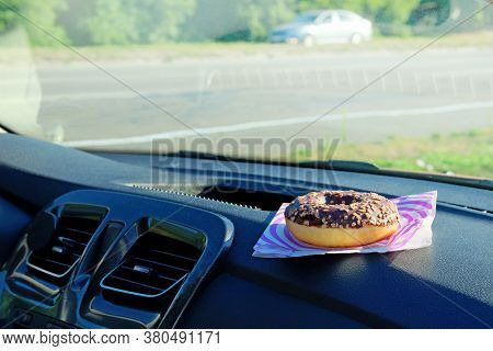 Donut For Lunch. Chocolate Nut Snack On Console In Auto. Lunch Break While Traveling By Car. Takeawa