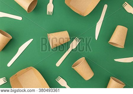 Disposable Paper Cups With Wooden Forks And Knives On Green Background. Zero Waste, Plastic Free Con