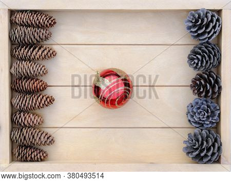 Merry Christmas Minimal Style Template. Red Christmas Ball And Pine Cones On A Wooden Tray. Holiday
