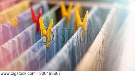 Colorful Clean Bed Linen And Towels After Washing Are Hung On The Bars Of The Dryer And Secured With