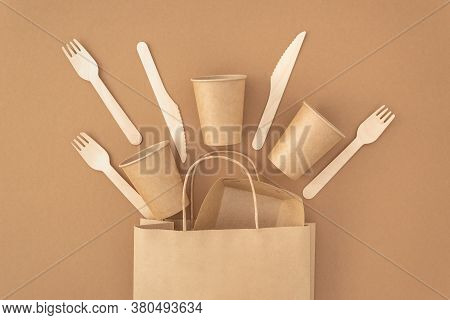 Zero Waste, Plastic Free Concept. Paper Bag With Disposable Paper Cups, Plate, Wooden Forks And Kniv