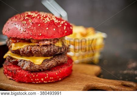 Homemade red sesame bun double bacon cheese burger. Served with french fries on wooden board. Tasty fastdood concept.