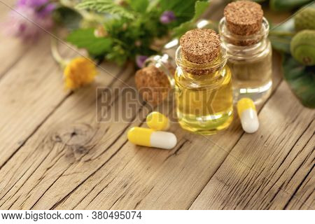 Essential Oil Or Oil For Natural Diseases Treatment In Glass Bottle On Wooden Table With Capsules Na