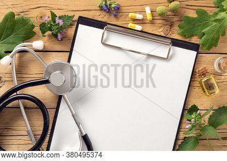 Alternative Medicine Clipboard With Stethoscope Various Plants Leaves Of Healing Herbs Capsules And