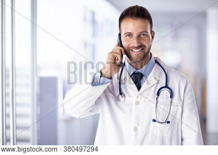Shot Of Happy Male Doctor Using Phone And Talking With Somebody While Standing On The Hospital's Foy