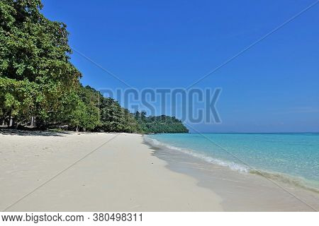 Tropical Beach On The Island. Pure White Sand, Aquamarine Waves With Foam, Green Trees On The Shore.