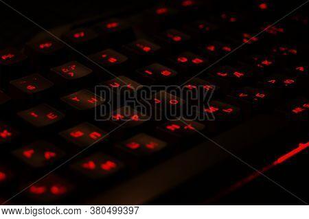 Backlit Gaming Keyboard Close Up. Black Keys With Red Illuminated Characters.
