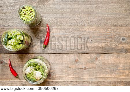 Top View Jars With Canned Green Vegetables And Chilli On A Wooden Kitchen Table. Preservation And Pr