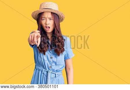 Young beautiful chinese girl wearing summer hat pointing displeased and frustrated to the camera, angry and furious with you