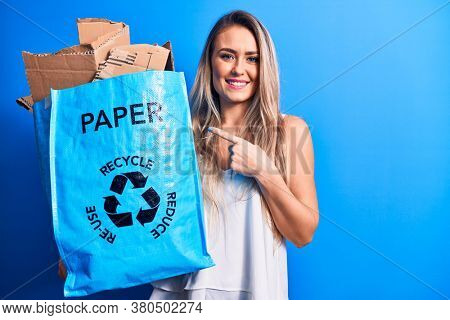 Young beautiful blonde woman recycling holding paper recycle bag full of paperboard smiling happy pointing with hand and finger