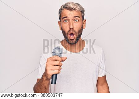 Handsome blond singer man with beard singing song using microphone over white background scared and amazed with open mouth for surprise, disbelief face