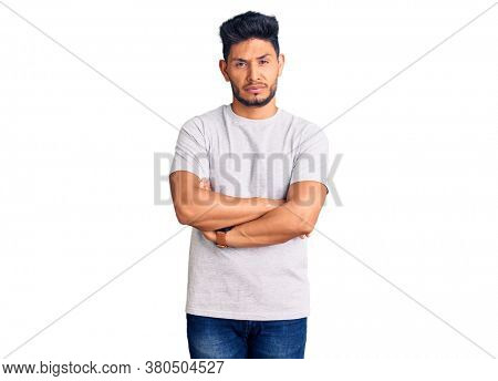 Handsome latin american young man wearing casual tshirt skeptic and nervous, disapproving expression on face with crossed arms. negative person.