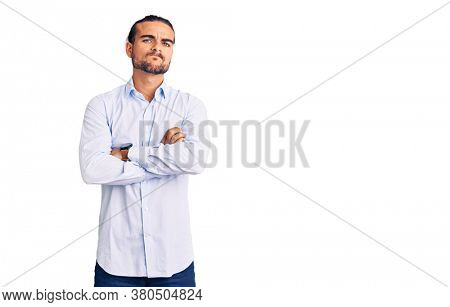 Young handsome man wearing business clothes skeptic and nervous, disapproving expression on face with crossed arms. negative person.