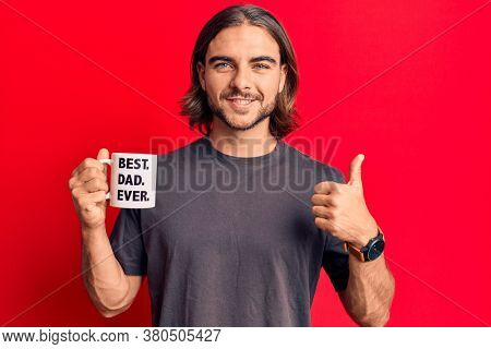 Young handsome man drinking mug of coffe with best dad ever message smiling happy and positive, thumb up doing excellent and approval sign