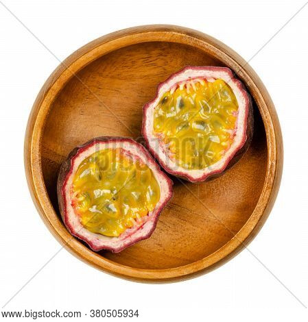 Fresh Passion Fruit Cut In Two Halves, In Wooden Bowl. Fruits With Purple Skin And Yellow Flesh With